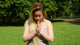 Young Attractive Asian Woman Prays And Nods Her Head In The Park - Close Up stock footage