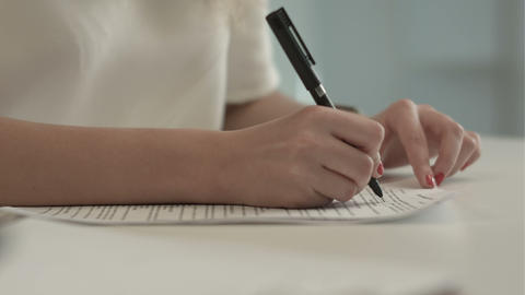 Businesswoman writes on a document at her office Footage