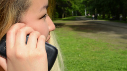 young asian attractive happy woman phones with somebody in the park - look from  Footage