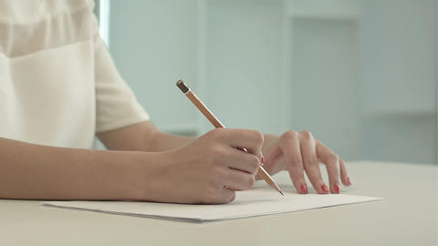Woman with pencil writing on paper Footage