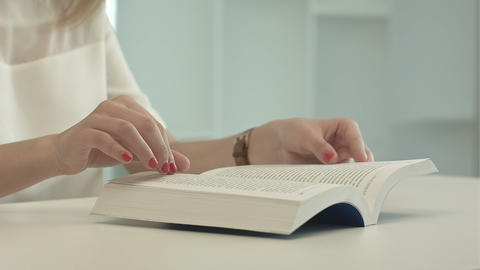 Woman sitting table and reading book Footage