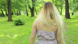 young attractive woman walks in the park - camera behind - steadicam Footage
