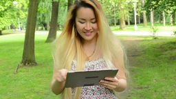 young asian attractive woman uses tablet - walks in the park - steadicam Footage