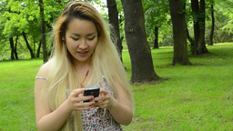 young asian attractive woman walks and chats on the phone in the park -steadicam Footage