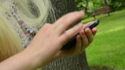 woman walks and works with smartphone in the park - detail - steadicam Footage