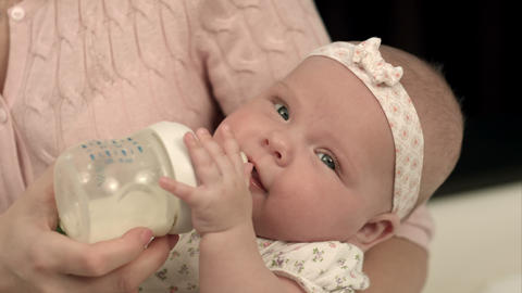 Young mother is feeding her baby milk Footage