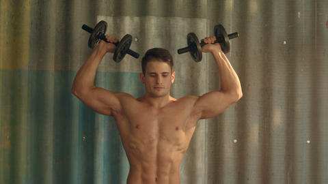 Muscular guy doing exercises with dumbbells Footage