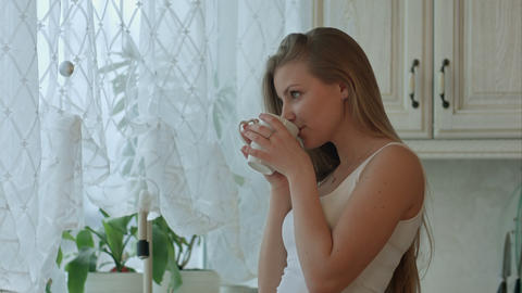 Young woman holding a cup of coffee in her kitchen Footage