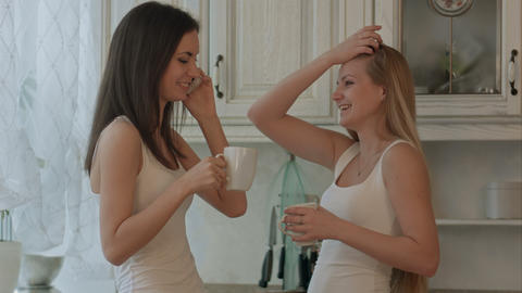 Two girls friend with phone drinking coffee or green tea on kitchen interior bac Footage