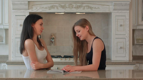 Two girls leaf through a magazine on the kitchen Footage