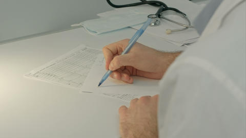 Doctor sitting on the desk with paper and working Footage