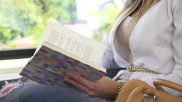 young attractive blonde woman traveling by train and reads a book - closeup Footage