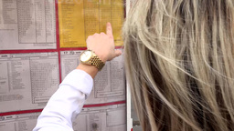 young attractive blonde woman looks at the timetables (tram) and finds her trans Footage