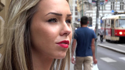 young attractive blonde woman looks around - urban street in the city with tram  Footage