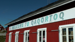 Greenland small town Qaqortoq 098 welcome banner on red house Footage