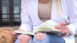 young attractive blonde woman reads book in front of university - closeup Footage