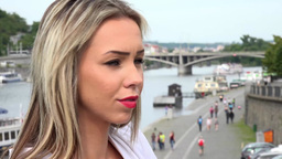 young attractive blonde woman looks around - bridges with river - walking people Footage