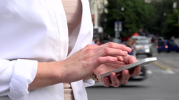 young attractive blonde woman works on smartphone - urban street with cars in th Footage