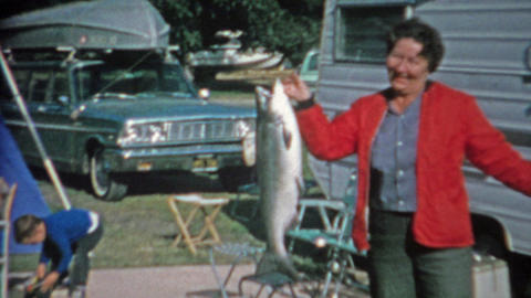 1966: Women catches big lake trout fish at trailer park campsite has trouble hol Footage