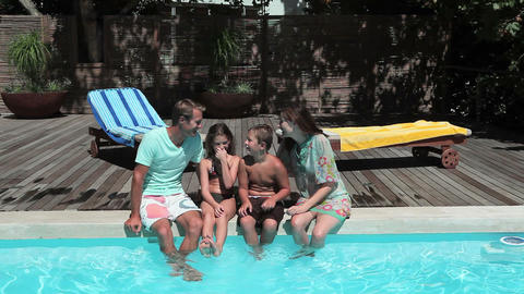 Family sitting on edge of swimming pool Stock Video Footage