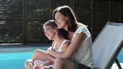 Mother and daughter hugging on lounger by pool Stock Video Footage