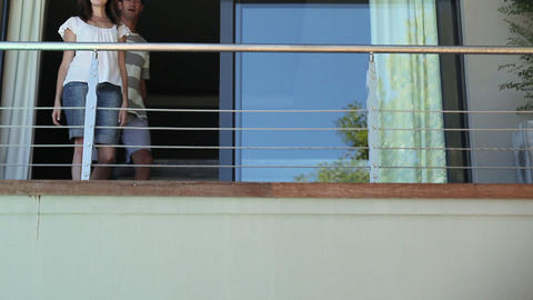 Couple on balcony of holiday home Stock Video Footage