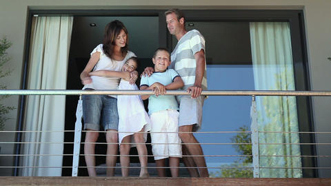 Family on balcony of holiday home Stock Video Footage