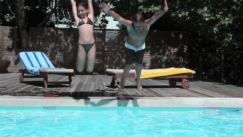 Boy and girl jumping into swimming pool Stock Video Footage