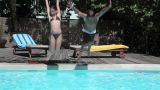 Boy and girl jumping into swimming pool Footage