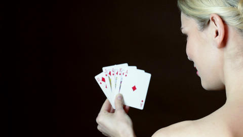 Young woman holding hand on cards and winking Stock Video Footage