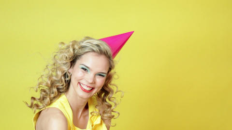 Young woman in party hat blowing party horn blower Stock Video Footage
