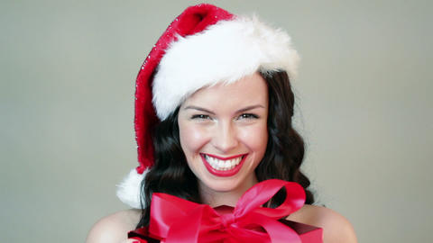 Happy young woman in santa hat with christmas gift Stock Video Footage
