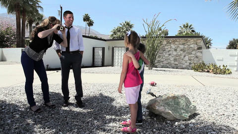 Family taking photographs outside home Stock Video Footage