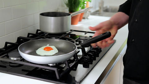 Frying an egg on the hob Stock Video Footage