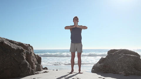 Young man doing yoga on beach Stock Video Footage