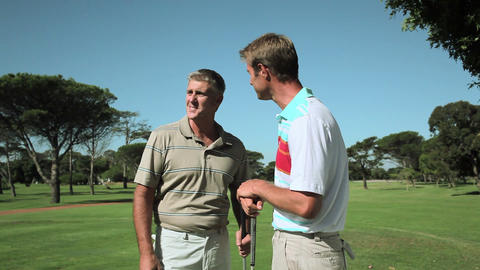 Mature men chatting on golf course Stock Video Footage