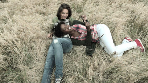 Two young female friends relaxing in field Stock Video Footage