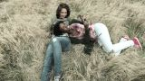 Two young female friends relaxing in field Footage