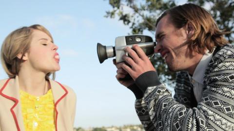 Man filming girlfriend blowing bubble gum Stock Video Footage