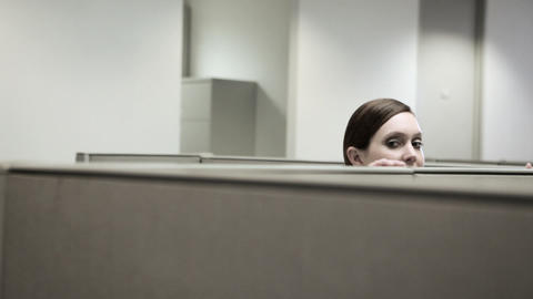 Woman hiding behind cubicle in office Stock Video Footage
