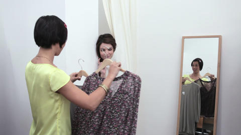 Sales assistant bringing clothes to woman in changing room Stock Video Footage