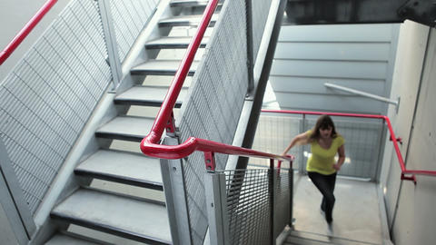 Young woman running up stairs and smiling at camera Stock Video Footage