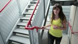 Young woman running up stairs and smiling at camera Footage