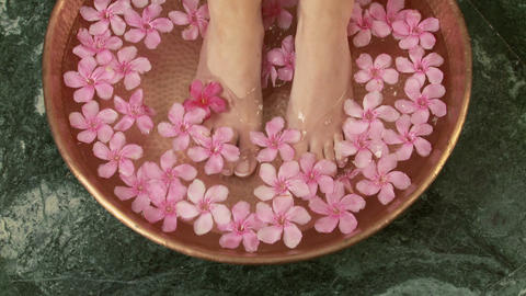 Woman placing feet in bowl of water and flowers Stock Video Footage