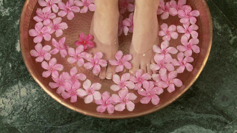 Woman placing feet in bowl of water and flowers Live Action