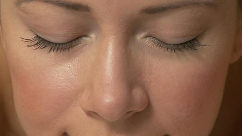 Face of young woman with eyes closed, zoom out to show... Stock Video Footage
