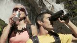 Couple by waterfall with binoculars and drinking bottle Footage