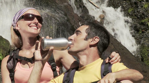 Couple by waterfall with binoculars and drinking bottle Stock Video Footage