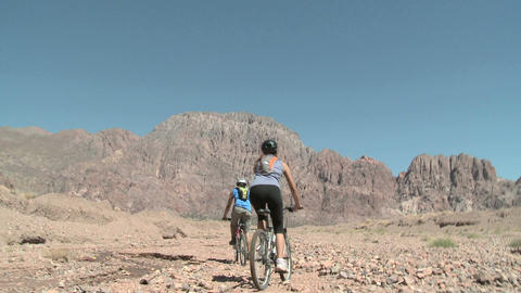 Couple cycling over rocky landscape Stock Video Footage