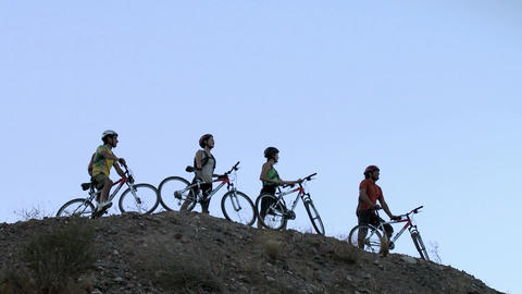 Mountain bikers standing on hill, zoom out Stock Video Footage